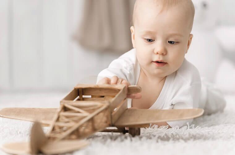 Babyfotos Baby spielt mit Flugzeug