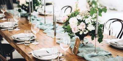 Gedeckter Hochzeitstisch aus Holz mit zartrosa Blumen und Kerzenständer