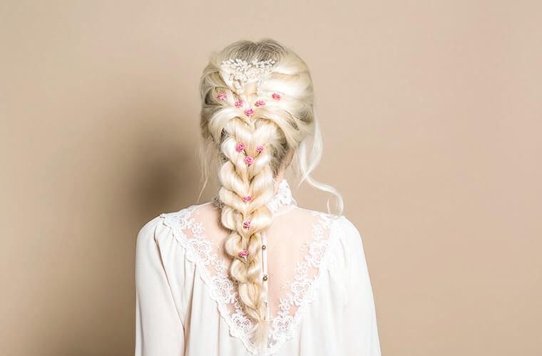 Blonde junge Braut mit geflochtenem langen Haar und Blumenverzierungen