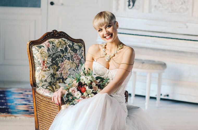 Junge Braut mit stylischer blonder Kurzhaarfrisur mit Blumen und antikem Sessel