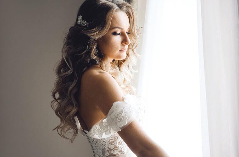 Hübsche Braut mit langen offenen gelockten Haaren in weissen Brautkleid