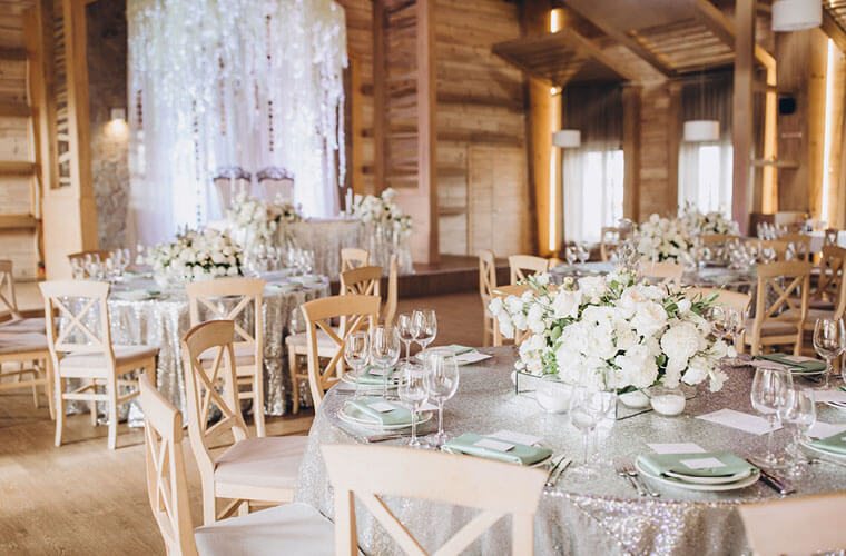 Rustikale Hochzeitslocation mit Holz, weiss gedeckten Tischen und Blumenbouquets