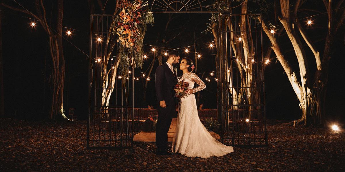 Vintagehochzeit, abens im Park, schickes Brautpaar in Anzug und langem weissen Kleid. Opulenter Blumenschmuck und schöne Lichterketten im Hintergrund.