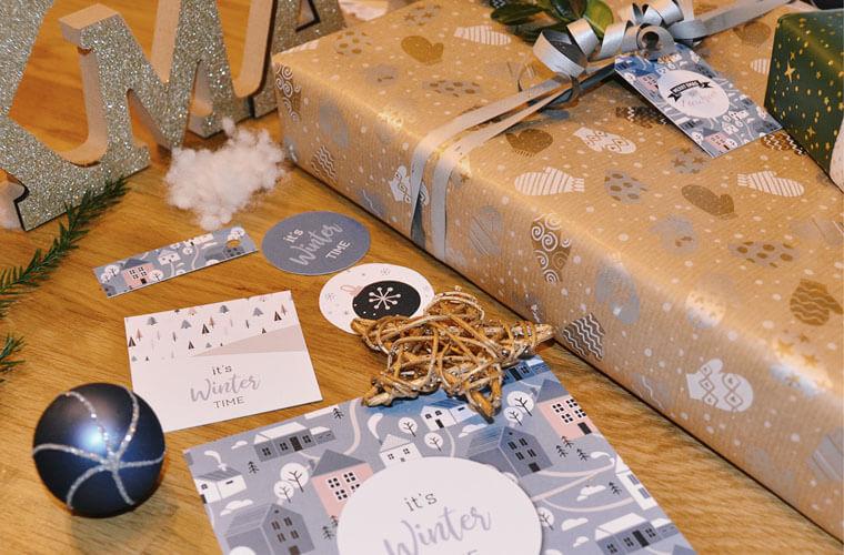 Geschenkskarte Winterstadt, blaue Elemente mit Holzstern und blauen Weihnachtskugeln